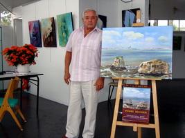 Pierre regnier devant ses toiles à l`exposition